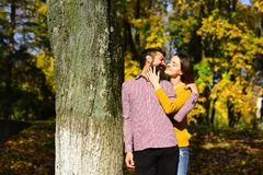 Couple in love plays near tree in autumn park. Girl and bearded guy or happy lovers on a date hug and cuddle. Man and women with happy faces on autumn trees stock photography