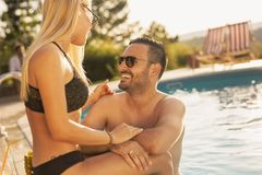 Couple having fun at a swimming pool. Couple in love at a poolside summer party, sitting at the edge of a swimming pool, sunbathing, drinking cocktails and royalty free stock photos