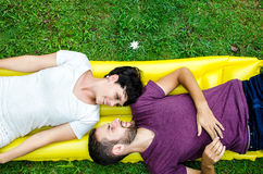 Couple in love. Portrait of happy couple lay on the grass Stock Image