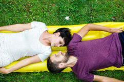 Couple in love. Portrait of happy couple lay on the grass Royalty Free Stock Images
