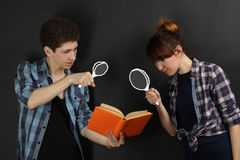 Couple in love. A couple in love posing on a black background. The guy with the girl read the book through a magnifying glass Royalty Free Stock Photography