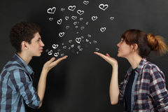 Couple in love. A couple in love posing on a black background. The guy with the girl send each other kisses in the shape of hearts Stock Image