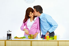 Couple in love prepare some food. Beautiful wife is preparing some food for lunch and her husband is kissing her in her cheek stock photo