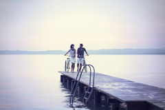 Couple in love pushing bike on a boardwalk at the lake Stock Images