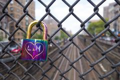 Shinny purple blue lock on a subway / train overpass fence with carved heart and initials. stock image