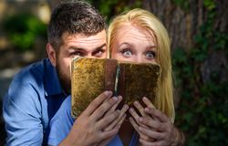 Couple in love read ancient book, dark background. Amazed faces of couple hidden by old untidy book. Man and women found shocking information in old notebook Stock Image