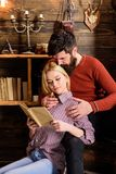Couple in love reading poetry in warm atmosphere. Couple in wooden vintage interior enjoy poetry. Romantic evening. Concept. Lady and men with beard on dreamy Royalty Free Stock Image