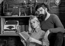 Couple in love reading poetry in warm atmosphere. Lady and man with beard on dreamy faces with book, reading romantic. Couple in love reading poetry in warm royalty free stock photography