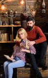 Couple in love reading poetry in warm atmosphere. Romantic evening concept. Lady and man with beard on dreamy faces hugs. Couple in love reading poetry in warm royalty free stock images