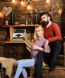 Couple in love reading poetry in warm atmosphere. Romantic evening concept. Couple in wooden vintage interior enjoy. Poetry. Lady and men with beard on dreamy royalty free stock photo