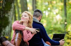 Couple in love relax in autumn forest with phone and laptop. happy girl dreaming outdoor. man sit with back. Spring mood. Couple in love relax in autumn forest royalty free stock photo