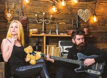 Couple in love on relaxed faces enjoy romantic atmosphere. Man play guitar while lady holds teddy bear in hands. Couple stock image