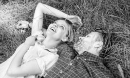 Couple in love relaxing lay at meadow. Nature fills them with freshness and peace. Man unshaven and girl lay on grass stock photography