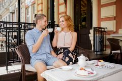 A couple in love resting in a cafe and eating dessert. Stock Photos