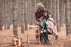 A couple in love in forest, a girl is drinking tea, a guy hides a girl with a warm blanket from behind. Royalty Free Stock Photo