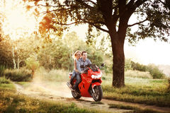 Couple in love rides a motorcycle in the park Stock Photography