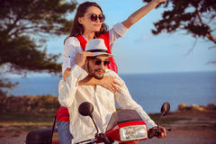 Couple in love riding a motorbike , Handsome guy and young sexy woman travel . Royalty Free Stock Images