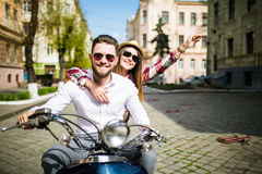 Couple in love riding a motorbike. Young riders enjoying themselves on trip. Couple in love riding a motorbike , Handsome guy and young sexy women travel Royalty Free Stock Photography