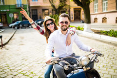 Couple in love riding a motorbike. Young riders enjoying themselves on trip. Couple in love riding a motorbike , Handsome guy and young sexy women travel Stock Images