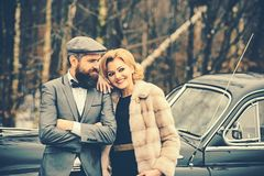 Couple in love on romantic date. Escort of girl by security. Retro collection car and auto repair by mechanic driver. Bearded men and sexy women in fur coat royalty free stock photo