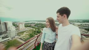 Couple in love on the roof. Girl with eyes closed. A guy brought his girlfriend on the roof to make a surprise. She opened her eyes and smiles. Man takes them stock video