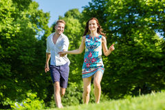 Couple in love running through park Royalty Free Stock Photos