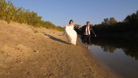 Couple in love runs along edge of river. Happy groom in suit and bride in white dress run on beach. Concept of a happy stock footage