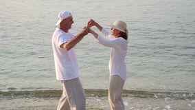Couple in love on the sandy beach in the sunset stock footage