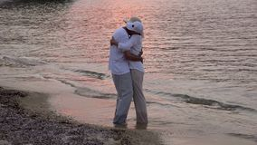 Couple in love on the sandy beach in the sunset stock video footage