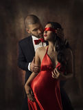 Couple in Love, Sexy Fashion Woman and Man, Girl with Red Band on Eyes Charming Boyfriend in Suit, Glamor Model Portrait. Valentine Day Lovers Sensual Games Stock Photo