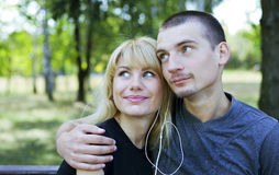 Couple in love sharing a song on one music player. Royalty Free Stock Image