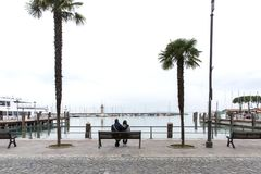 Couple in love on the shores of Lake Garda, Desenzano di Garda, Italy. In love couple on the waterfront. Couple hugging on a bench royalty free stock photos
