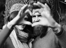 Couple in love shows heart sign with fingers. Man and women with smiling faces on tree background. Dating and autumn love concept. Girl in pink hat and bearded Royalty Free Stock Photography