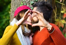 Couple in love shows heart sign with fingers. Romance and fall mood concept. Man and women with blured faces on tree background. Girl in pink hat and bearded Stock Photo