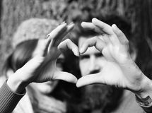 Couple in love shows heart sign with fingers. Lovers. Girl in pink hat and bearded guy or happy lovers on a date. Man and women with happy faces on tree Royalty Free Stock Photo