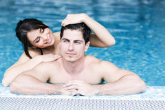 Couple in love by the side of the pool. Sexy beautiful couple in love relaxing in the water of a swimming pool Royalty Free Stock Photos