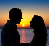 Couple in love silhouette at lake sunset. Couple in love back light silhouette at lake orange sunset Royalty Free Stock Photos