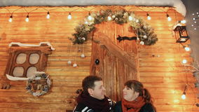 A couple in love sit on the porch of a wooden fairy-tale house and enjoy each other. Christmas and New Year theme. A couple in love sit on the porch of a wooden stock footage