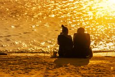 Couple love sit relaxing on the tropical beach during sunset time