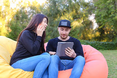 Couple in love sit and talk in armchairs, guy holds in hand elec Royalty Free Stock Photography