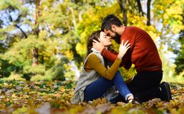 Couple in love sitting on autumn fallen leaves royalty free stock photo