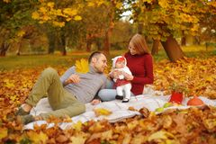 Couple in love sitting on autumn fallen leaves in a park, sit on the rug , enjoying a beautiful autumn day. Happy royalty free stock images