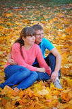 Couple in love sitting on the autumn leaves Stock Photography