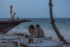 Couple in love sitting on the beach on background of an old boat tonight. Travel around Africa. royalty free stock photos