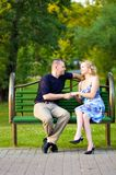 Couple in love sitting at a bench Stock Image