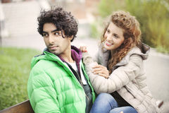 Couple in love sitting on a bench in city stock image
