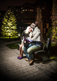 couple in love sitting on bench covering with plaid Stock Photo