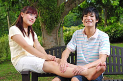 Couple in Love sitting on bench giving massages Royalty Free Stock Photo