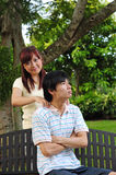 Couple in Love sitting on bench giving massages 2 Stock Images