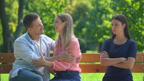 Couple in love sitting on bench hugging and chatting, ignoring their friend stock footage
